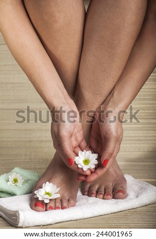 Female feet and hands with drops of water, towel and flowers. Copy space. - stock photo
