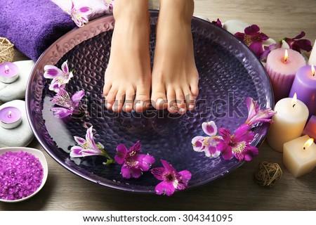 Female feet at spa pedicure procedure - stock photo