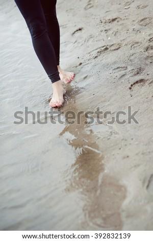 Female feet barefoot, beach, water. - stock photo