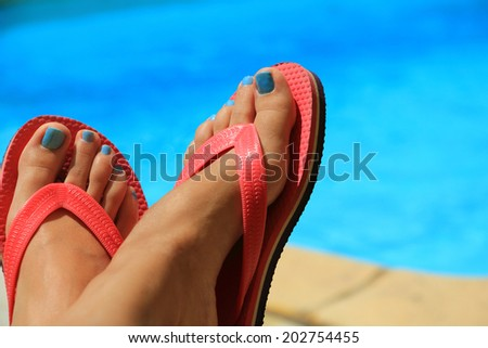 Female feet by the poolside blue waters  - stock photo