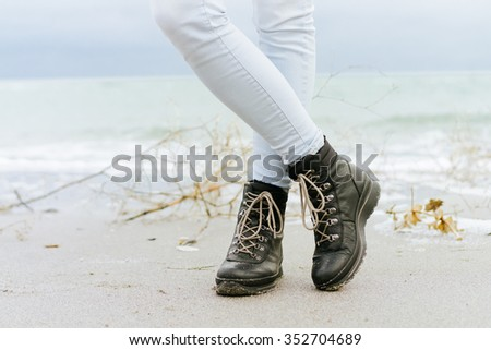 Female feet in blue jeans and black winter boots standing in the sand at the beach - stock photo