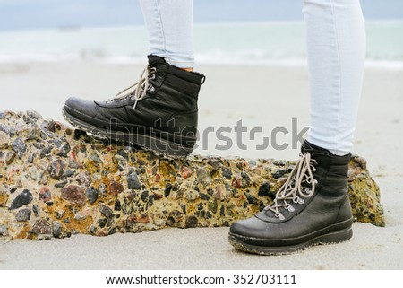 Female feet in blue jeans and black winter boots standing on a stone against the sea - stock photo