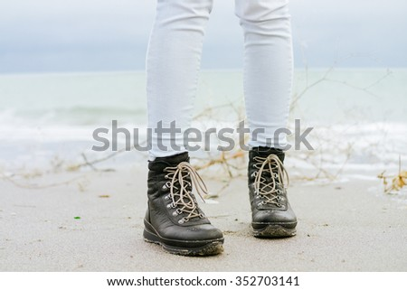 Female feet in blue jeans and black winter boots standing on the beach - stock photo
