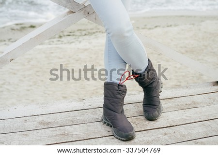 Female feet in blue jeans and sporting boots standing on a wooden platform on the beach in autumn - stock photo