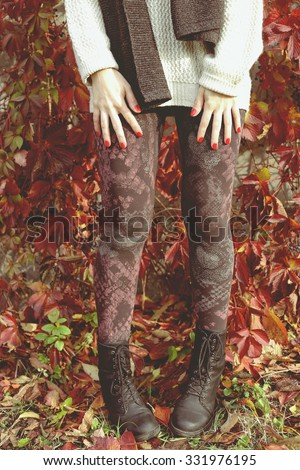 Female feet in brown leggings. Stylish Girl. Street fashion, street style. Warm sweater with long sleeves. A light sweater and scarf. Autumn time, cool. On the street. - stock photo