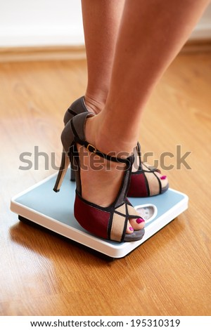 Female feet in color stilettos with weight scale on wooden floor - stock photo
