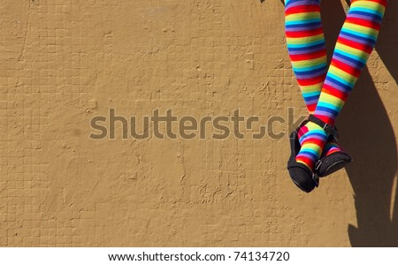 female feet in colorful socks on the background of a gray wall. - stock photo