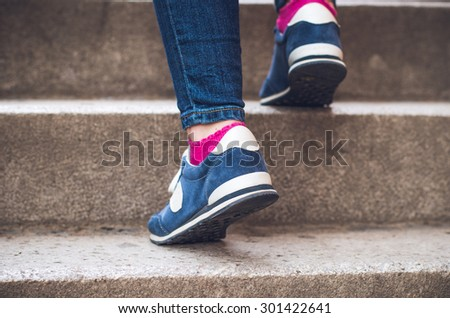 Female feet in denim sneakers on the stairs - stock photo