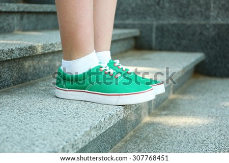 Female feet in green gumshoes on stone stairs