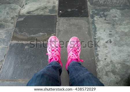 Female feet in jeans and sports shoes - stock photo