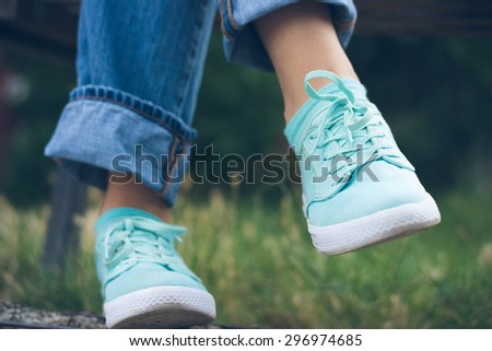 Female feet in jeans and sports shoes in the park close up. Woman sitting on a bench near the green grass. Rest after walking. - stock photo