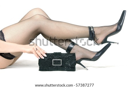 Female feet in shoes on a high heel and a handbag, side view on  white background - stock photo