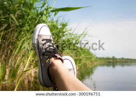 Female feet in sneakers on the background of a river landscape sunny summer day - stock photo