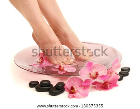 Female feet in spa bowl with water, isolated on white - stock photo