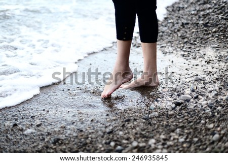 Female feet in the cold sea water at sunset