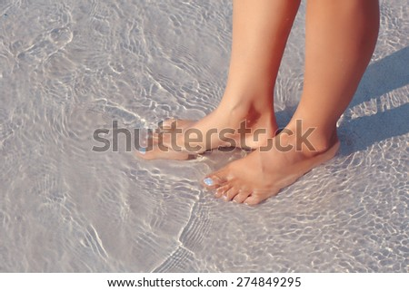 Female feet in water on the beach, white sand - stock photo