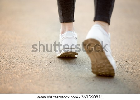 Female feet in white sneakers running on concrete, jogger practicing, close-up. Healthy, active lifestyle concepts, copy space - stock photo