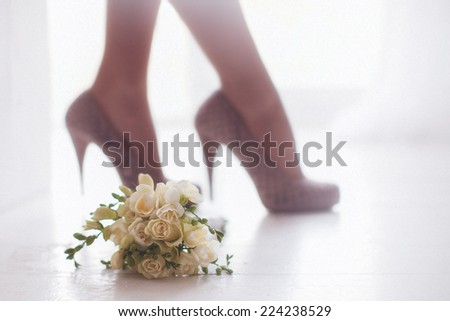 female feet in white wedding sandals with a bouquet - stock photo