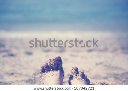 female feet on a sandy beach, instagram effect - stock photo