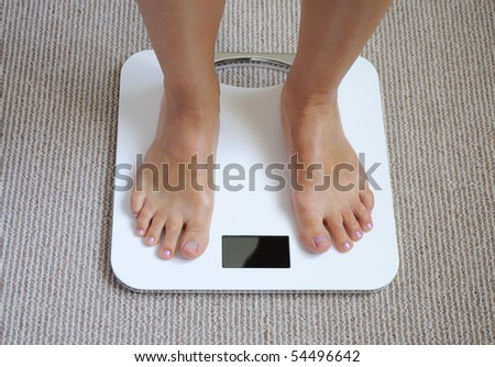 Female feet on bathroom scale - stock photo