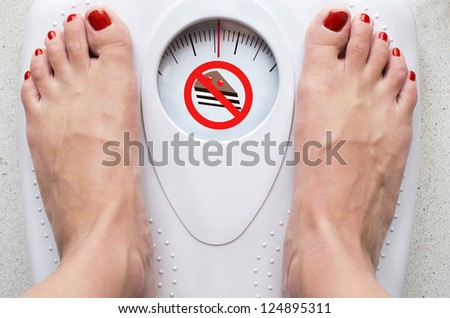Female feet on bathroom scale with forbidden cake symbol - stock photo