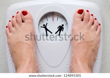 Female feet on bathroom scale with silhouette symbols - stock photo