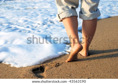 female feet on sand and in sea foam - stock photo