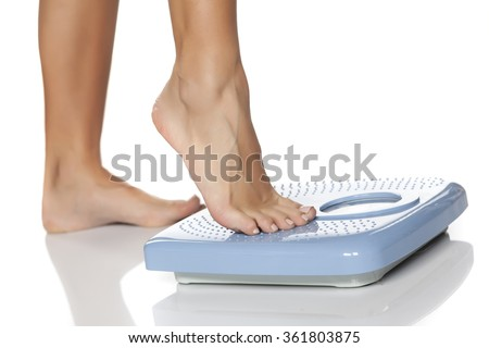 female feet on scale - stock photo