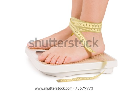 Female feet on scales isolated - stock photo