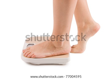 Female feet on scales isolated