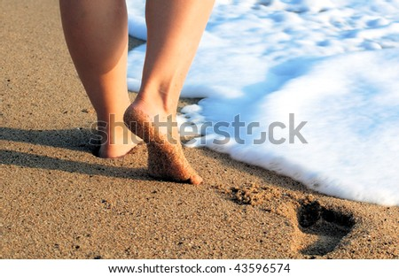 female feet on sea sand and white foam with a wave