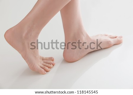 Female feet on white floor - stock photo