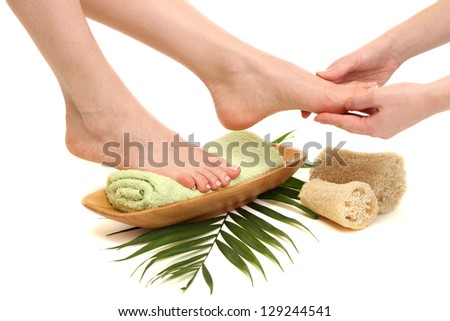 Female feet receiving a massage, isolated on white - stock photo