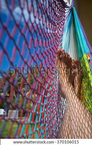 Female feet relaxed in colorful hammock