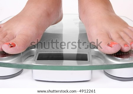 Female feet standing on a bathroom scale - stock photo