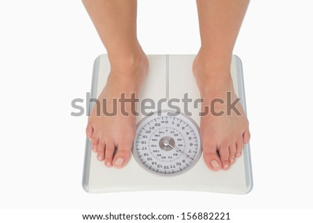 Female feet standing on a white scales on white background - stock photo