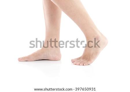 Female feet walking on white background isolated - stock photo