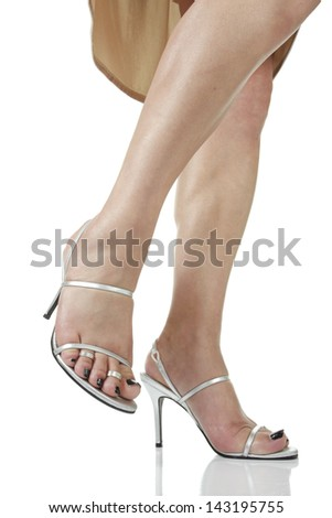 Female  feet wearing silver high heel shoes over white