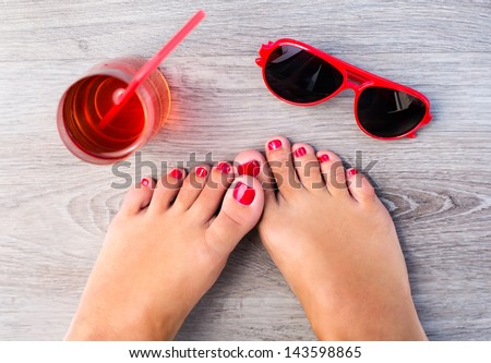 Female feet with color pedicure near with glasses and fresh drink - stock photo