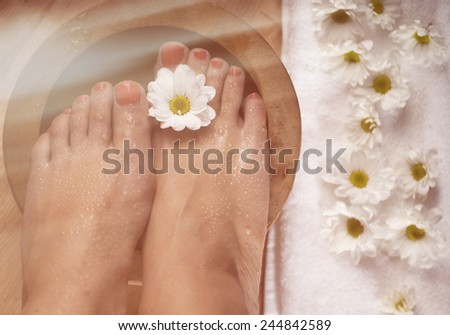 Female feet with drops of water, spa bowl, towel and flowers. Special lighting effect. - stock photo