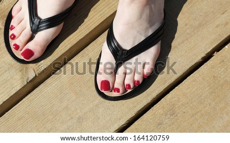 Female feet with flip-flops outdoor red nail - stock photo