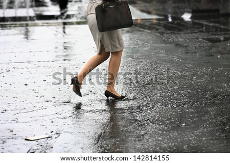 female feet with heels shoes walk on water when it rains - stock photo