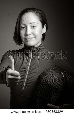 Female fencer showing thumbs up sign - stock photo