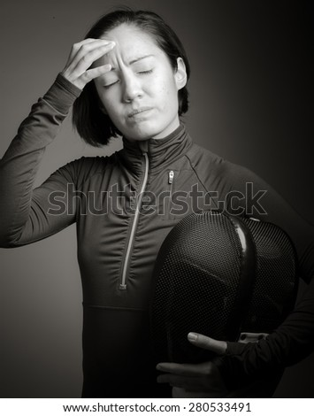 Female fencer suffering from headache - stock photo