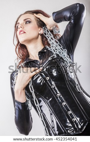 female fetishist with shiny rubber corset and steel chains