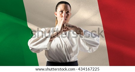 Female fighter performing hand salute against digitally generated italy national flag - stock photo