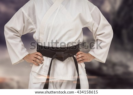 Female fighter standing with hand on hip against rock crashing down from cliff