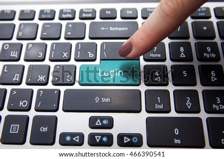 Female finger presses on a computer keyboard on the Enter key, the blue button with the inscription Log in