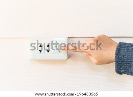 female finger switching light on or off.Electrical element to turn light and electricity on and off