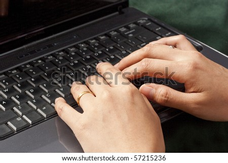 Female fingers typing a document on the black laptop - stock photo